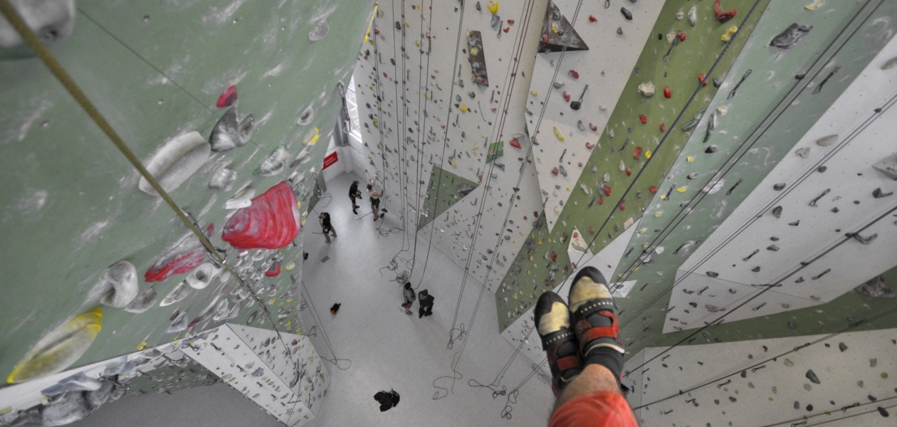 Foto vom Ablassen aus der Kletterwand beim Kletterkurs in der Kletterhalle