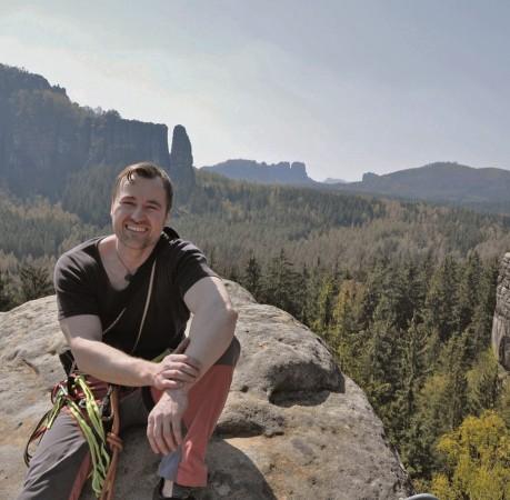 Foto eines zufriedenen Kletterers auf einem Felsturm in der Sächsichen Schweiz